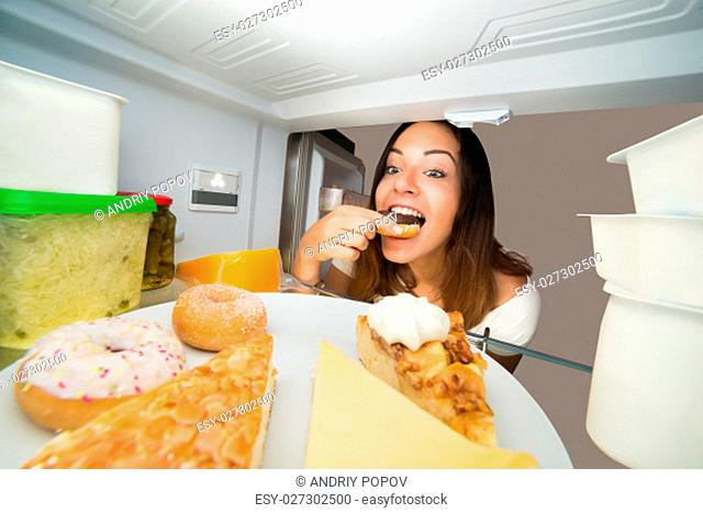 Young Woman Enjoy Eating Donut From Open Refrigerator