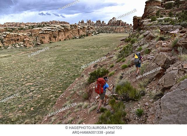 Two female backpackers on trail overlooking The Needles in Canyonlands National Park, Moab, Utah, USA