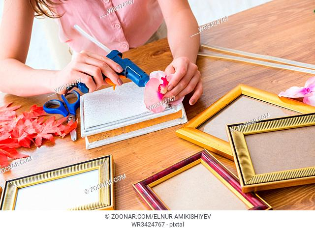 Woman decorating picture frame in scrapbooking concept