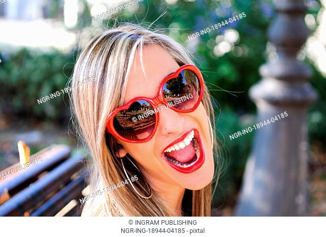 Funny girl with red heart glasses in a park