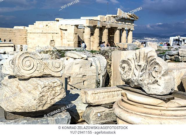 Remains of ancient columns in Acropolis of Athens city, Greece. Monumental gateway called Propylaea on background