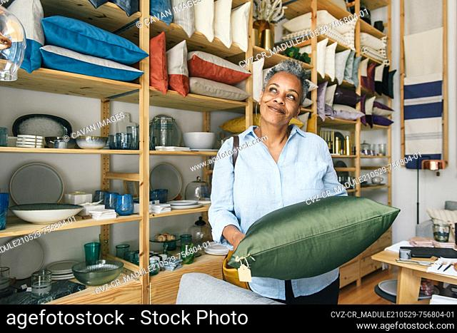 Woman looking off to the side and thinking on purchase while shopping