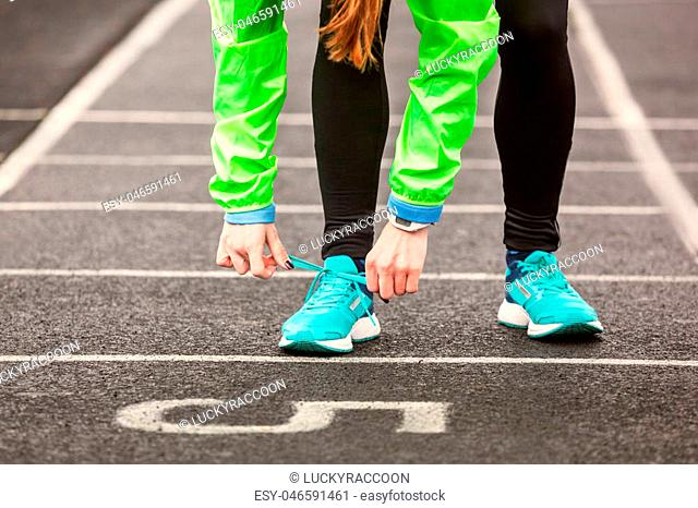 Cropped shot of a woman tying her shoelaces before running on a stadium