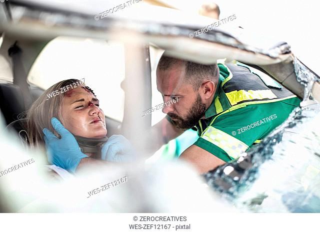 Paramedic helping car crash victim after accident