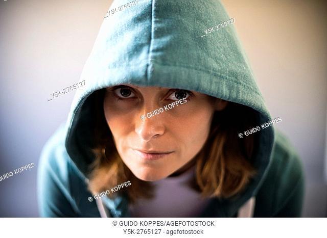 Tilburg, Netherlands. Studio portrait of a mid adult caucasian female wearing a hoody