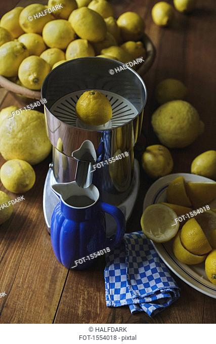 Blue pitcher and electric juicer by lemons on wooden table