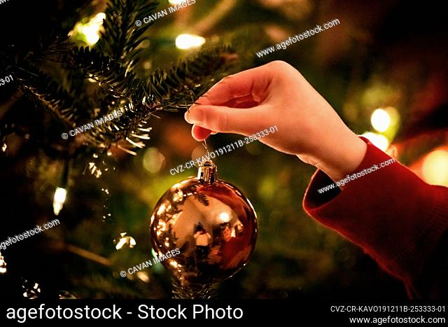 small hand placing a ornament onto a Christmas tree
