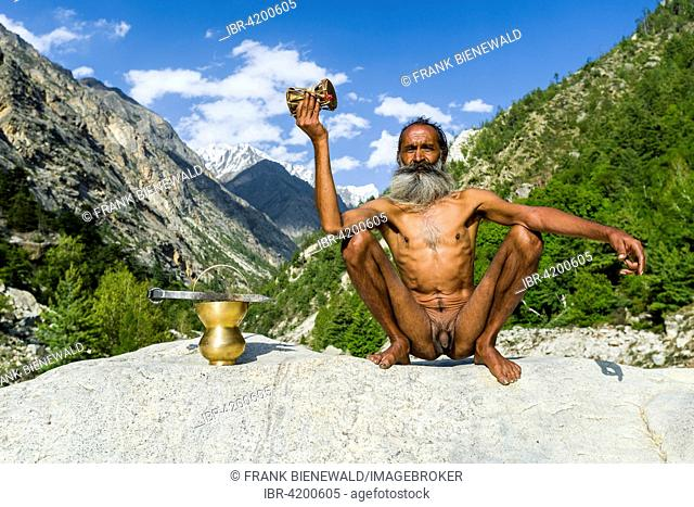 Mahant Naomi Giri, a 52 years old Sadhu, is sitting on a rock at the banks of the holy river Ganges, using his drum and praying, Gangotri, Uttarakhand, India