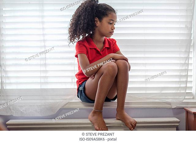 Girl sitting on windowsill looking sad, looking away