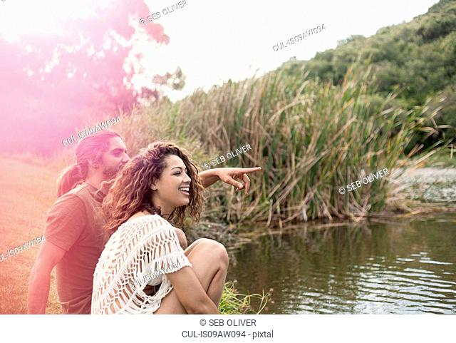 Couple sitting by river looking away smiling, pointing