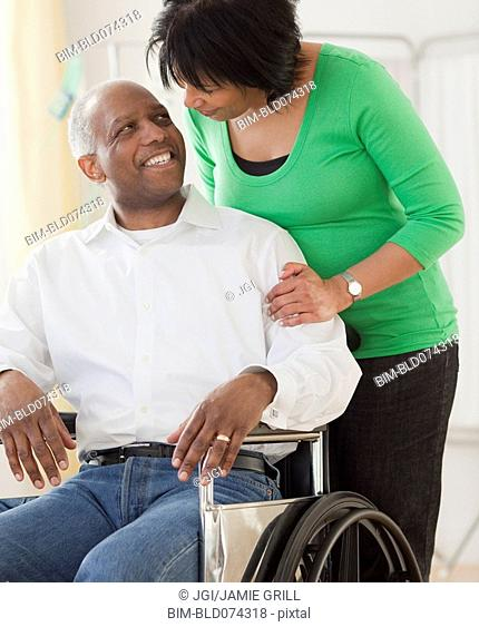 African woman pushing husband in wheelchair