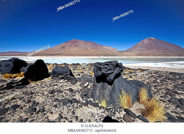 Black volcanic rocks near the Laguna Verde, In the background volcanoes Juriques and Llicancabur, South Lipez, Bolivia, South America