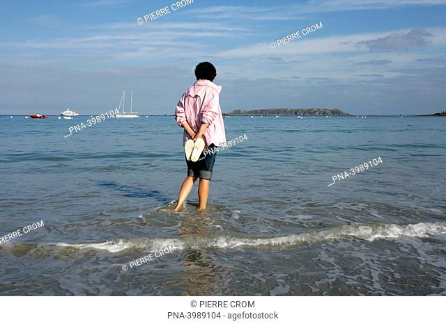 Woman paddling in sea, Brittany, France