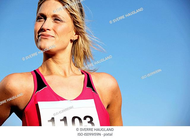 Mid adult woman in sports vest against blue sky