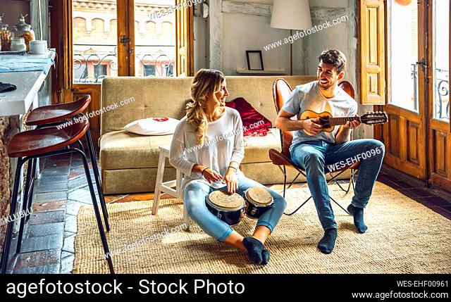 Happy young couple playing duet with drums and guitar in living room at home