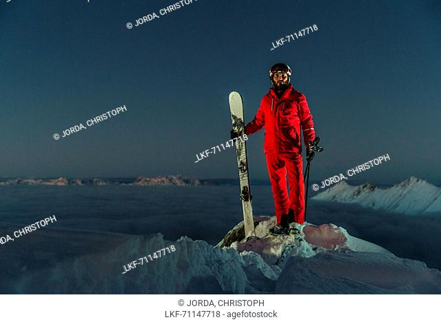 Young male skier standing on the top of a mountain over the clouds at night, Kaprun, Salzburg, Austria