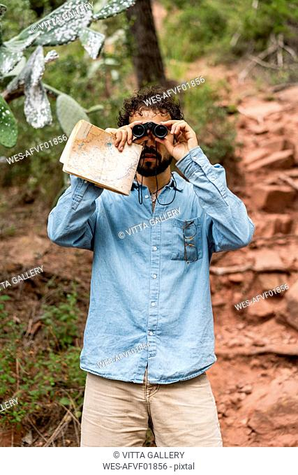 Young man standing in nature, looking through binoculars, holding map