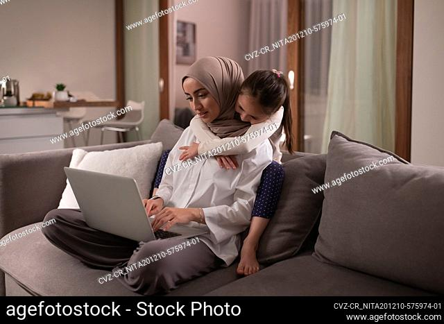 Muslim mother with daughter working on couch