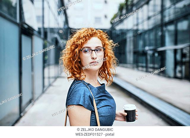 Young businesswoman holding take out coffee