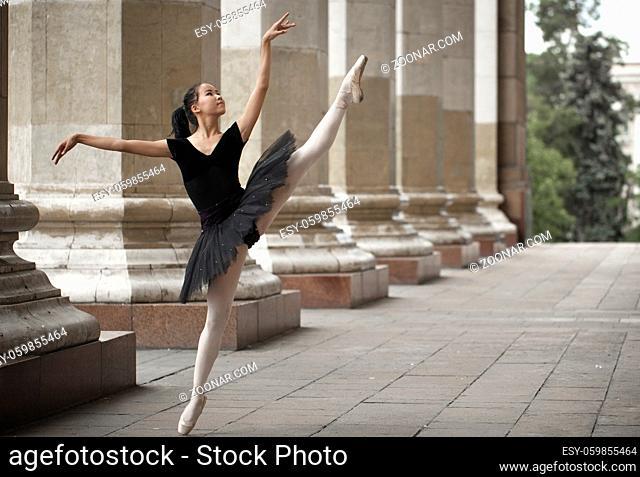 Girl ballerina flats standing on tiptoes on the street