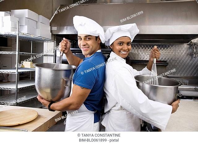 Multi-ethnic pastry chefs mixing batter back to back