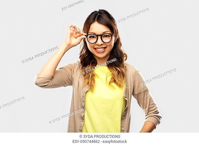 happy asian woman in glasses or student