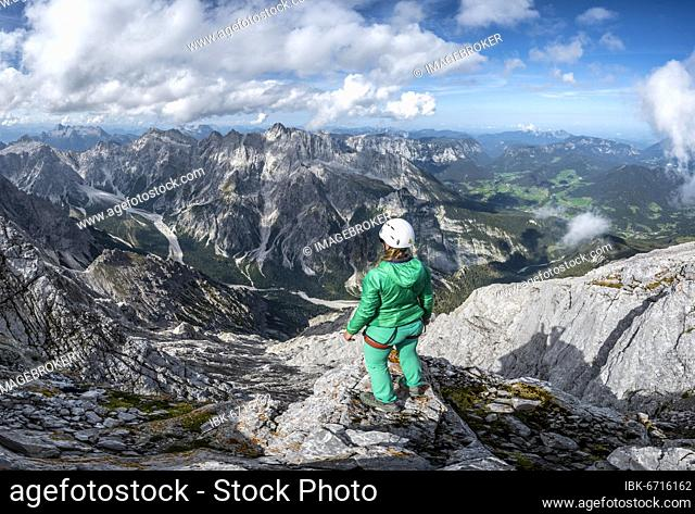 Hiker with helmet at the summit of the Watzmann, view over mountains, mountain range Hochkalterstock with Blaueisspitze and Hochkalter