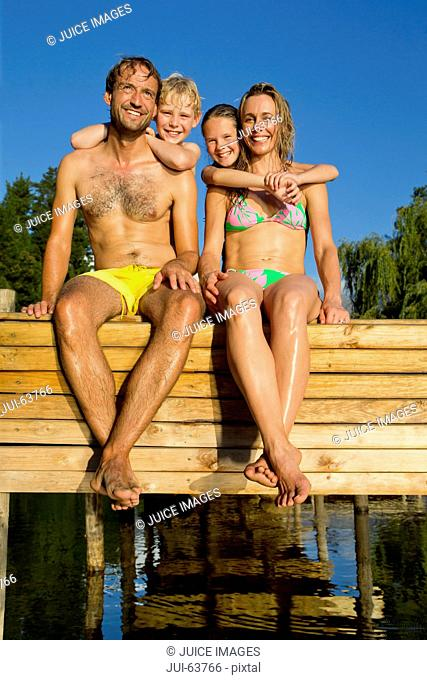 Portrait of happy family sat on jetty beside lake