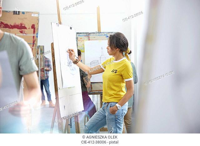 Female artist sketching at easel in art class studio