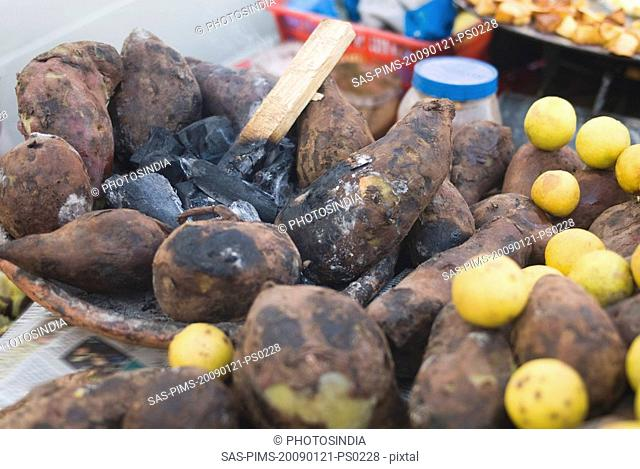 Close-up of sweet potatoes with lemons at a chaat stall, New Delhi, India