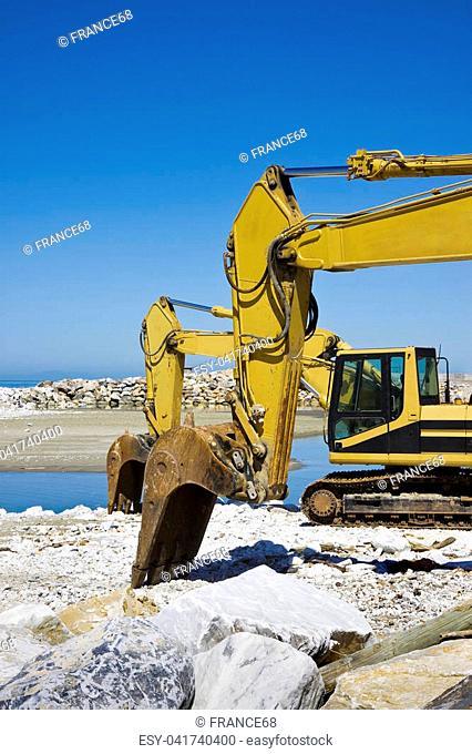Yellow diggers on the seashore building a breakwater