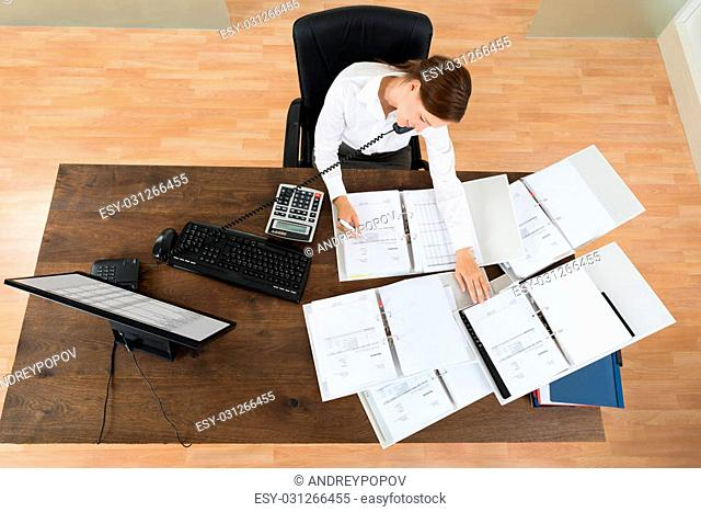 High Angle View Of Young Businesswoman Attending Call While Calculating Finance At Desk