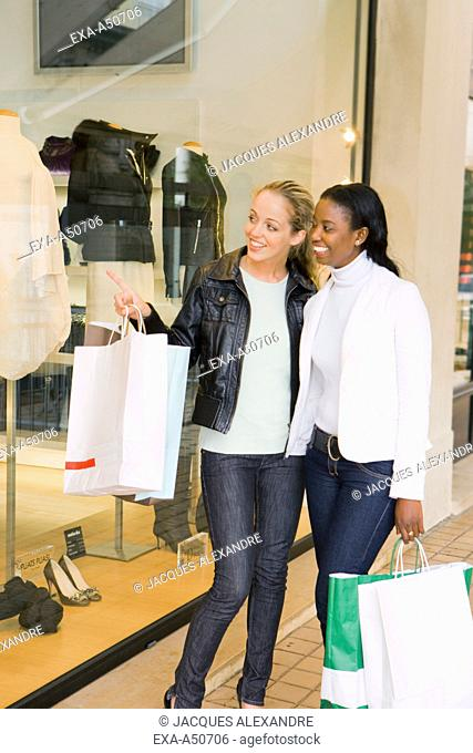 Caucasian and african woman shopping in the city together and looking through a shop display