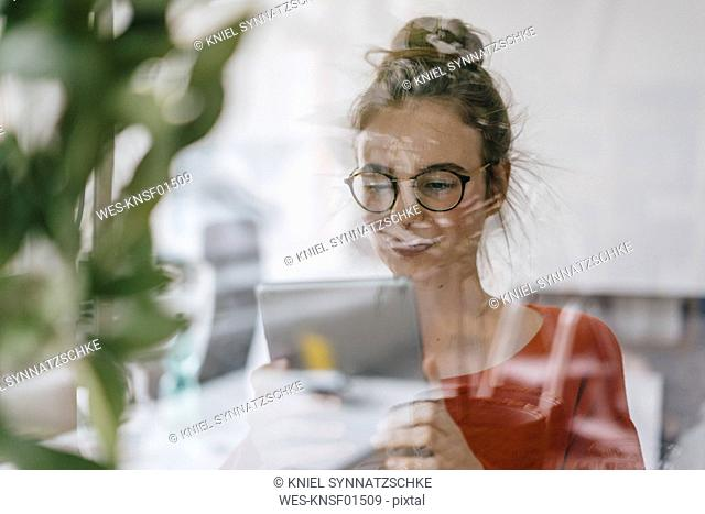 Young woman using tablet behind glass pane