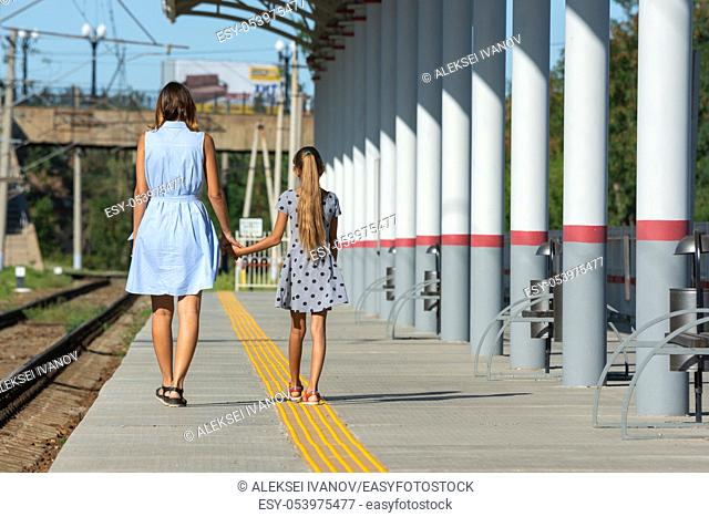Young beautiful girl and teenage daughter walk from the camera on the empty platform of the train station