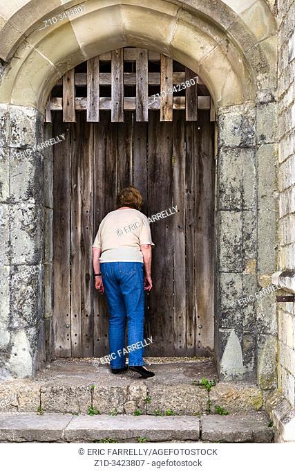 nosey woman. . looking through cracks in medieval door. Southampton City Walls England UK