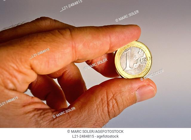 One euro coin between the fingers of one hand