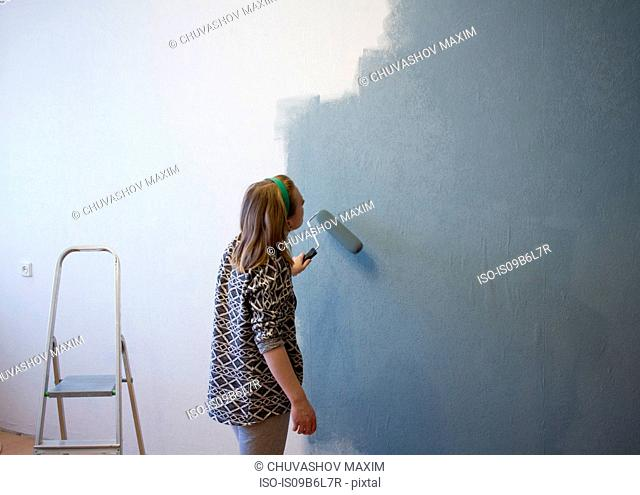 Young woman applying grey paint to interior wall at home