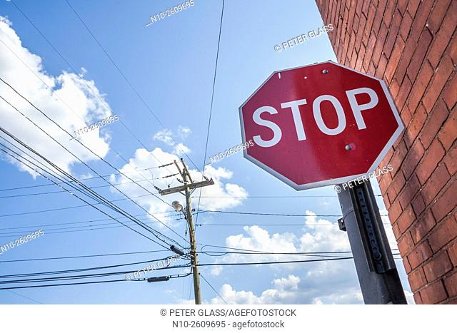 """""""""""""""""""""""Stop"""""""" sign next to power lines and a brick wall"""