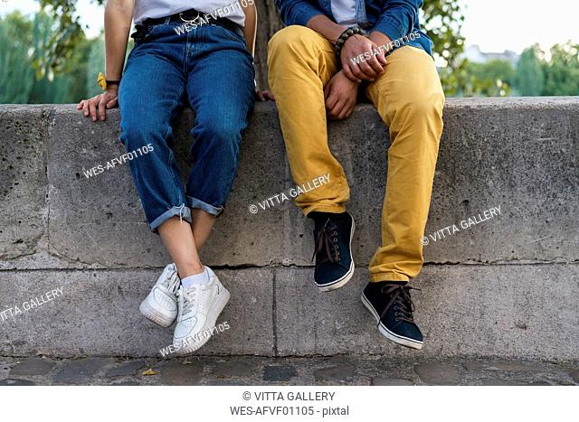 Legs of a couple sitting on a wall