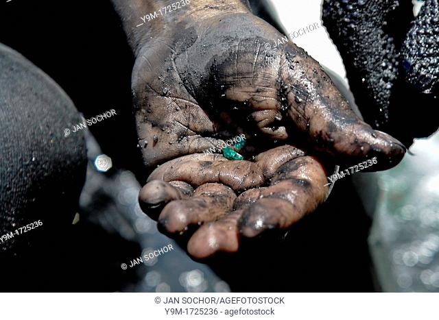 A miner shows a rough emerald found in the mine of Muzo, Colombia, 21 April 2006  Despite of a persisting civil war conflict and related difficulties Colombia...
