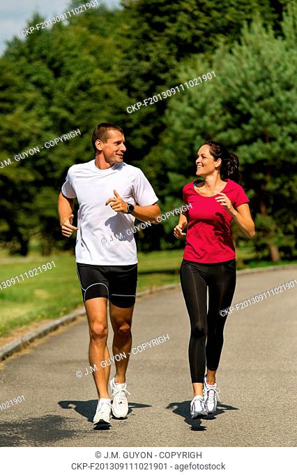 Sporty Caucasian couple running in park