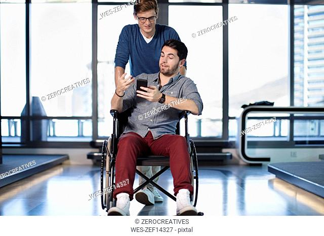 Man talking to handicapped colleague in wheelchair