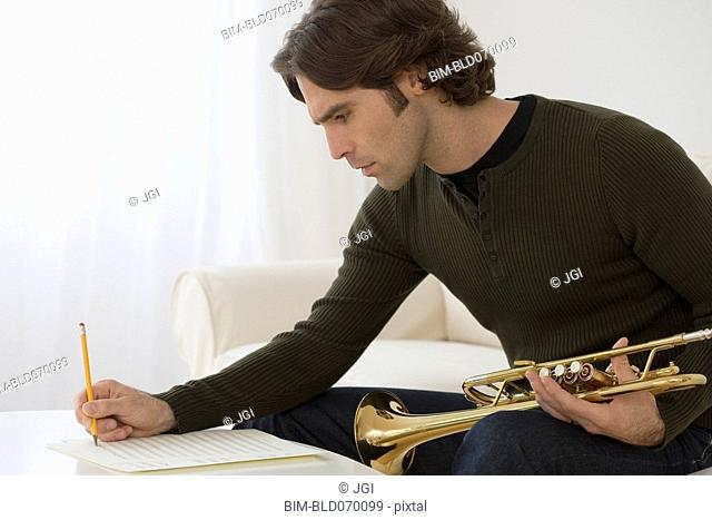 Hispanic man composing trumpet music
