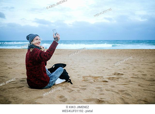 Smiling young woman sitting on the beach in winter using cell phone