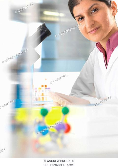 Portrait of female scientist testing blood sample using microscope