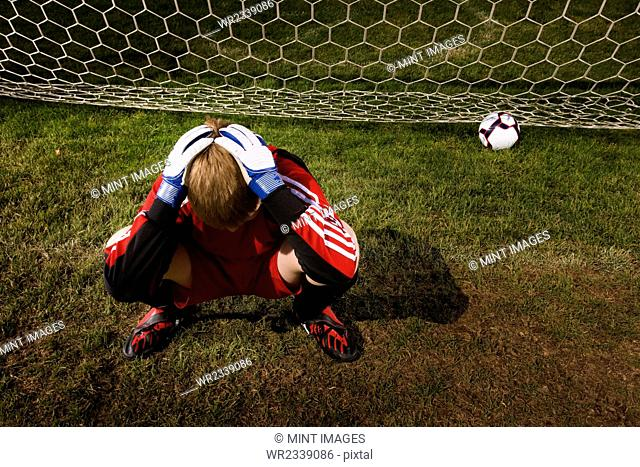 A goal keeper with his head in his hands, and a soccer ball at the back of the goal net