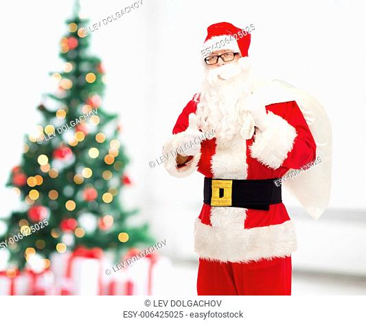 christmas, holidays, gesture and people concept - man in costume of santa claus with bag showing thumbs up over living room with tree
