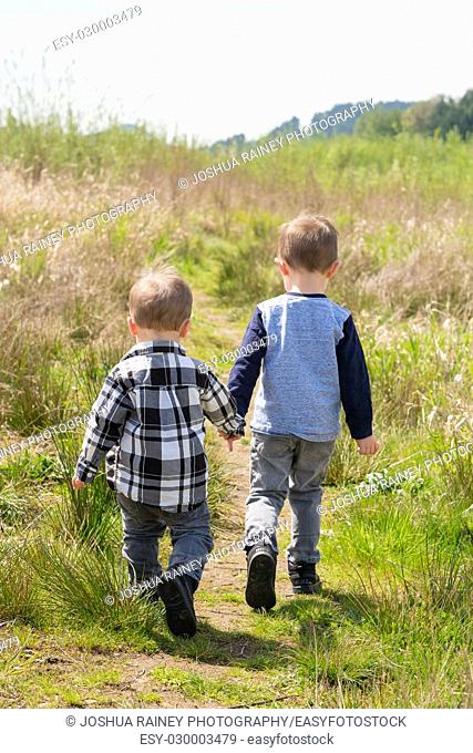 Lifestyle portrait of two young brothers playing together and exploring in a field outdoors in Oregon