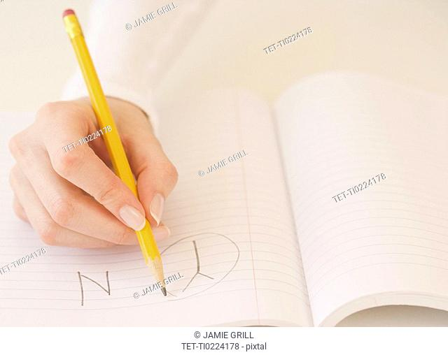 Woman circling the letter Y in notebook